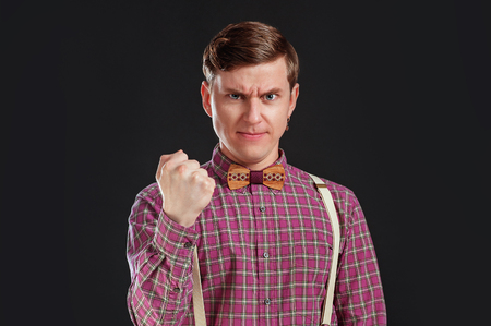 Feeling so angry! Angry young man in vintage shirt and bow tie with hairstyle looking at camera and making a face and show a fist on black background. People emotions Business Education Teacher