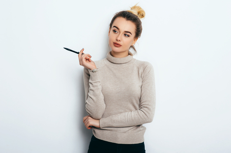 Portrait of cheerful woman with appealing smile, having hair bun in sweater isolated on white background holding pen and have a great idea. Beautiful female showing emotions. People Beauty Fashion