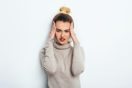Close up isolated portrait of young stressed angry woman holding hands on head. Negative human emotions, headache face expressions. Lifestyle Fashion Beauty People Business concepts.