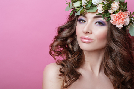 Beautiful young woman with curly hair and flower wreath on her head on pink background Beauty girl with flowers hairstyle Perfect makeup Beauty fashion People Skin Stock Photo