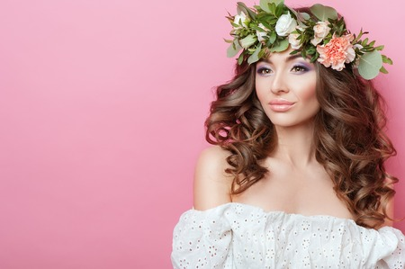 Portrait of beautiful young sexual sensual woman with perfect skin make up curly hair and flowers on head on pink background. Wreath of flowers Spring Summer Fashion Lifestyle People Copy space
