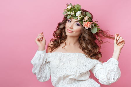 Portrait of beautiful young sexual sensual woman with perfect skin make up curly hair and flowers on head on pink background. Wreath of flowers Spring Summer Fashion Lifestyle People concepts.