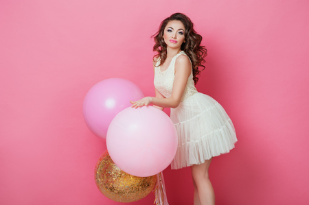 Cheerful Beautiful young girl in dress with sparkle and pink helium balloons enjoying birthday photoshoot dancing and smiling on pink background Cute woman posing in studio. Fashion Lifestyle Emotions Stock Photo
