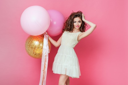 Beauty girl with colorful air balloons laughing over pink background. Beautiful Happy Young woman on birthday holiday party. Fashion model having fun, playing and celebrating with pastel color balloon Stock Photo