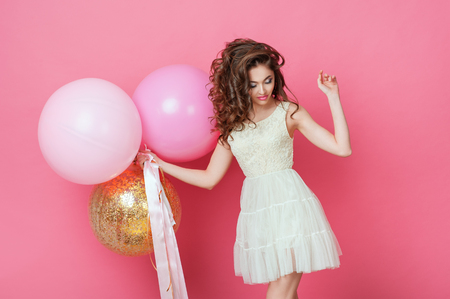 Beauty girl with colorful air balloons laughing over pink background. Beautiful Happy Young woman on birthday holiday party. Dancing model having fun, playing and celebrating with pastel color balloon