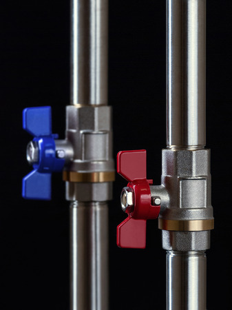 Valves for hot and cold water on a black background