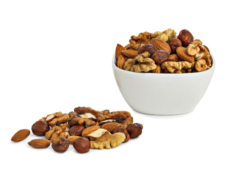 A handful of nuts and saucer with nuts isolated on white background