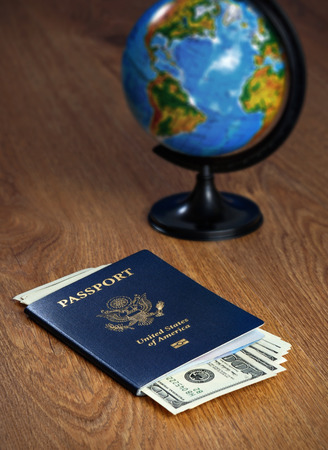 American passport with dollars and the globe