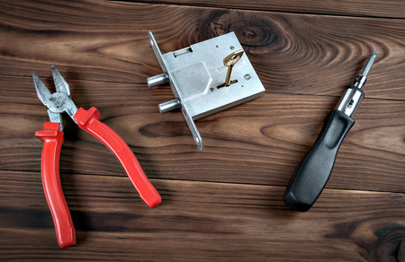craft material tinker: Door lock and tools located on a wooden surface