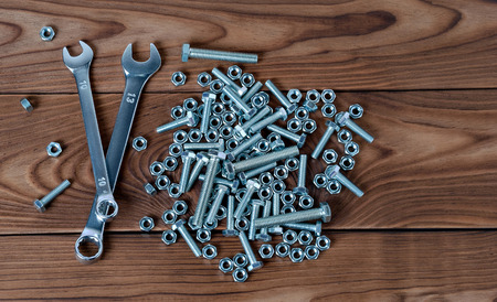 Spanners and nuts with bolts are located on a wooden surface