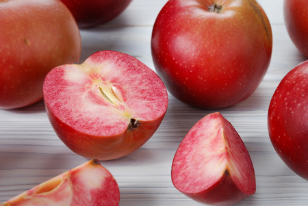 Red apples called Redlove are located on a wooden surface