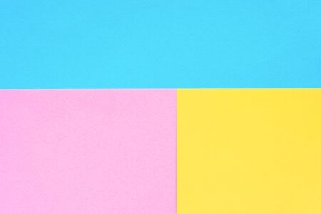 Blue, yellow and pink colored paper. Geometric empty paper background of three tones for copy space.