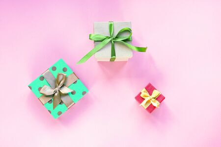 Three gifts in boxes with bow-knot on pink background. Spring holidays, birthday concept. Top view, flat lay.