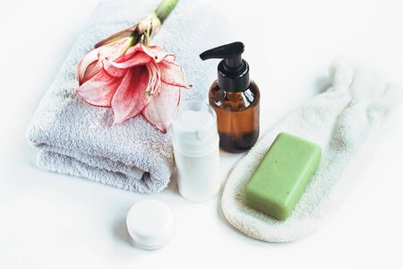 Cosmetics, skin tonic, towel and handmade soap on white table. Spa treatments and skin care concept.