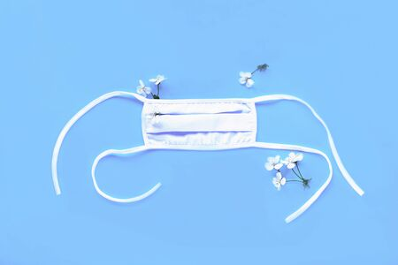 White protective medical mask on blue background with cherry flowers. Covid-19 concept. Top view, flat lay