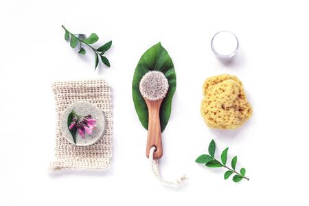 Wooden brush, handmade soap, face cream and natural sponge. Eco-friendly spa, massage, peeling and hydration products. White background, top view, flat lay, copy space.