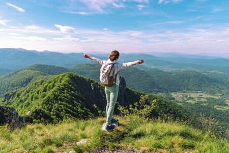 Girl tourist with a backpack stands on the edge of a cliff with outstretched arms. Hiking, tourism, freedom concept. 版權商用圖片 - 147878651
