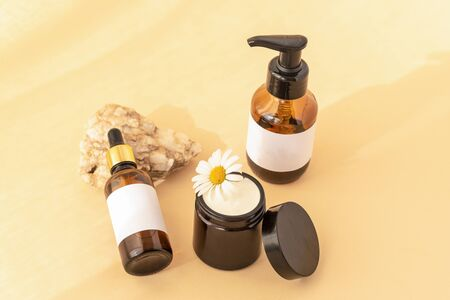 Beauty products: wash gel, cream jar, serum on natural stone, yellow background, top view. Natural cosmetics and skin care concept. Archivio Fotografico