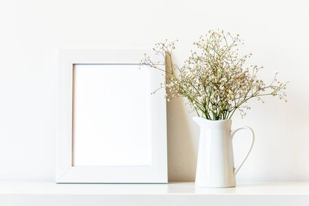 Blank picture frame and Gypsophila flowers in white jug, mock up.