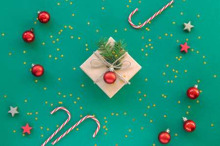 Christmas gift in a box with confetti and red baubles on green background. New year concept. Top view, flat lay, copy space. Stock Photo