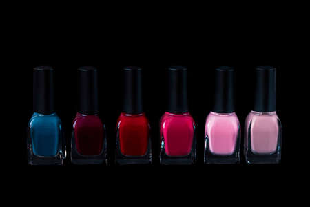 Collection of nail polishes isolated on black, front view