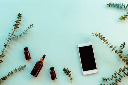 Essential oils and serum in dark glass bottles next to the mobile phone, eucalyptus branches on light blue background. Natural cosmetics and aromatherapy concept. Top view, flat lay, copy space.