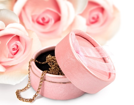 giftbox with a gold chain on a background of roses Stock Photo - 12608674