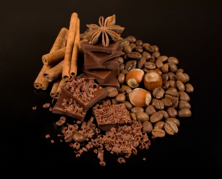 chocolate, coffee , cinnamon and nuts on black background