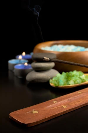 Spa: incense sticks , sea salt and candles on a black background photo