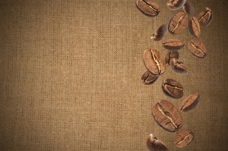 texture with falling coffee beans on burlap background