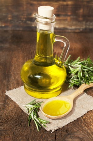 olive oil and rosemary on a wooden background