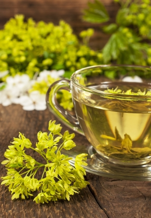 glass cup is of green tea with herbs on the wooden background  photo