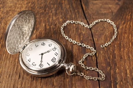 vintage pocket watch with chain on a wooden background  photo