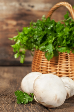 mushrooms and a basket with fresh parsley on wooden background photo