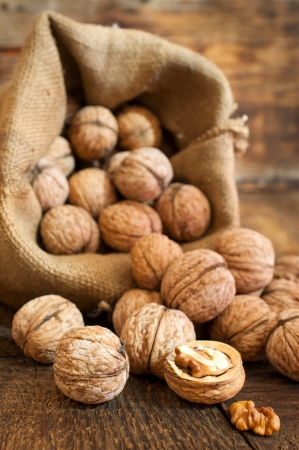 walnuts in a burlap bag on a wooden background
