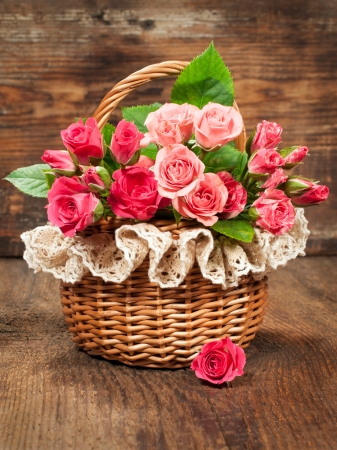 pink roses in a vintage basket on  wooden background photo