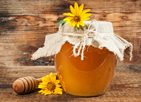 Sweet honey with yellow daisies on a wooden background