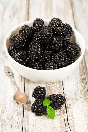 ripe blackberries on wooden background close-up   photo