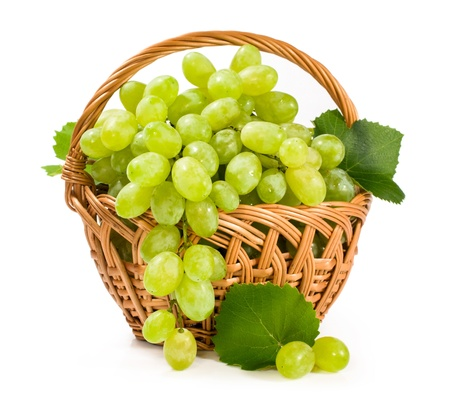 green grapes in a wicker basket isolated on white