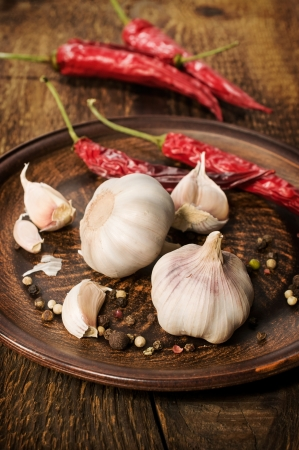garlic and red chili peppers on a wooden background photo