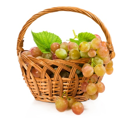 ripe grapes in a wicker basket isolated on white photo
