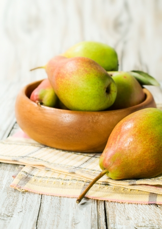 Ripe pears in a wooden bowl close-up photo