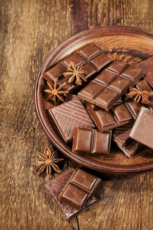 chocolate and star anise in a clay plate on a wooden background photo