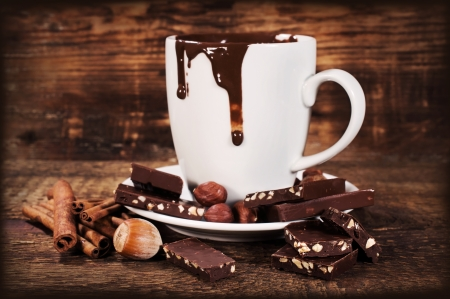 cup of hot chocolate with nuts and cinnamon on wooden background