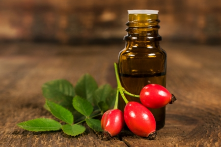 bottle of essential oil of rose hips on wooden background Stock Photo - 22990508