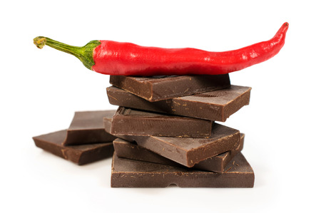 broken black chocolate with chili pepper isolated on white photo
