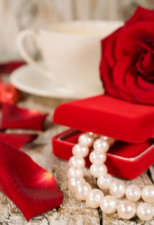 background valentines day : a pearl necklace and rose petals photo