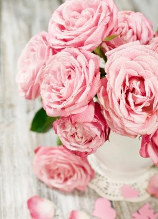 花瓶塗装木製の背景にピンクのバラの花束