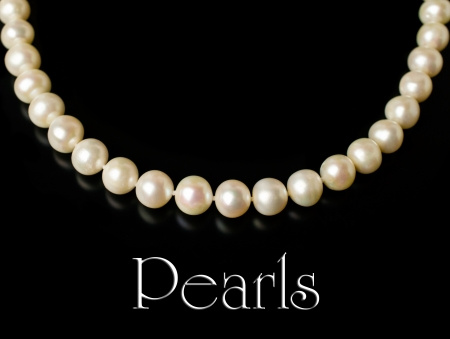 Necklace of white pearls isolated on black photo