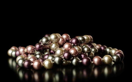 colored pearls on a black background with reflection